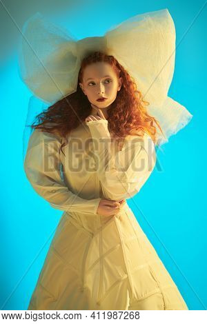 Portrait of a sophisticated fashion model girl with lush red curly hair posing in a light haute couture dress and a huge bow. Studio portrait. Fashion art.