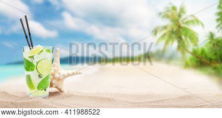 Fresh cold cocktail on tropical beach with palms and bright sand. Summer sea vacation and travel concept with copy space