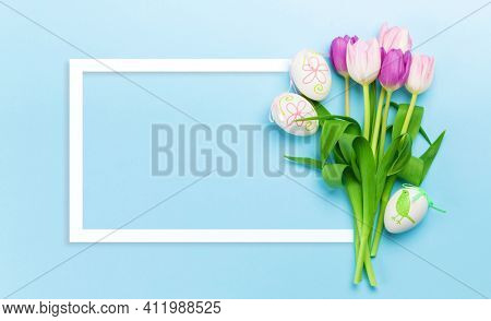 Easter greeting card with easter eggs and tulip flowers over blue background. Top view flat lay with frame for your greetings