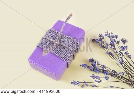 Natural Handmade Soaps And Lavender Flowers On A Light Yellow Background. Close-up.