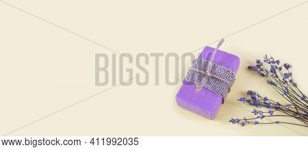 Natural Handmade Soaps And Lavender Flowers On A Light Yellow Background. Banner. Copy Space.