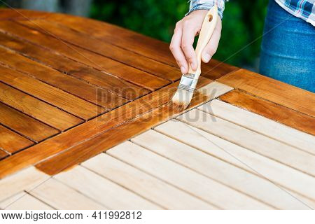 Renovation Of A Garden Table With A Brush And Oil By A Young Girl On The Terrace