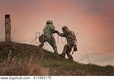 A Man In A Gas Mask And A Chemical Protection Suit Helps Another Person To Walk. Post-apocalypse Aft
