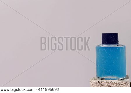 Blue Bottle With After Shave Gel For Men With Water Drops On The Stone On Gray Background. Cosmetic,
