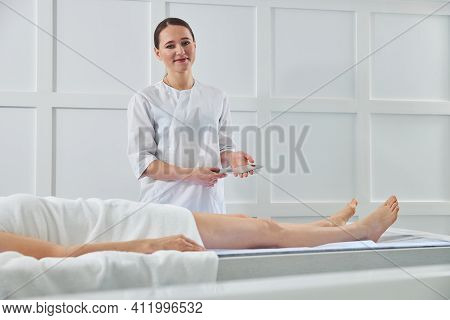 Charming Masseuse Standing Near Client And Holding Metal Tool