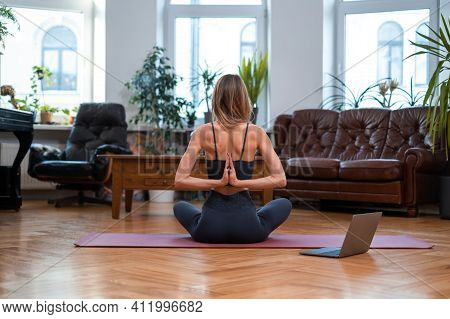 Calm Portrait Of A Sportive Female Model She Does Workout On Mat. Backview Of Sportsperson Keeping H