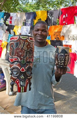 MAPUTO, MOZAMBIQUE - APRIL 29: Unidentified man selling traditional african masks on the market in Maputo, Mozambique on April 29, 2012. The local market is one of the tourists attraction of the city.