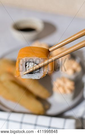 Japanese Sushi Rolls With Black Chopsticks. Sushi Rolls With Cream, Maki, Chopsticks And Soy Sauce