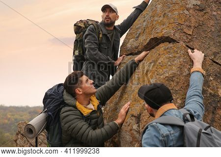 Group Of Hikers With Backpacks Climbing Up Mountains