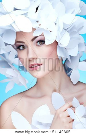 Wonderful girl in a hat from paper white butterflies. On a blue background. Beauty Face