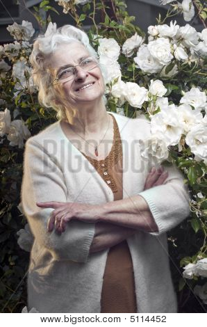 Happy Senior Lady In The Rose Garden Looking Up