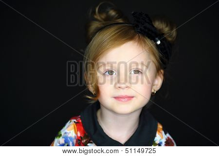 Facial portrait of a little girl with hair dressing on a dark background