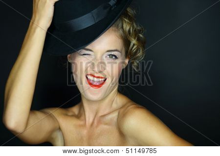 A young woman with bare shoulders and black hat winks on a dark background