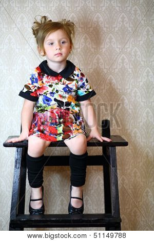 A little girl in variegated dress sitting on a black stand