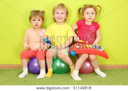 Two girls and a boy sitting on a colorful balls, one of the girls playing on the metallophone