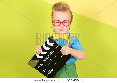 A boy in a bright clothing and red big glasses with a clapstick in his hands