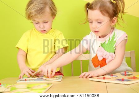 Little boy and girl with pigtails playing a board game together