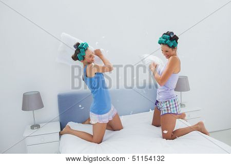 Girls in hair rollers having pillow fight in bed at sleepover