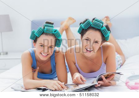 Girls in hair rollers holding magazines and smiling at camera at sleepover