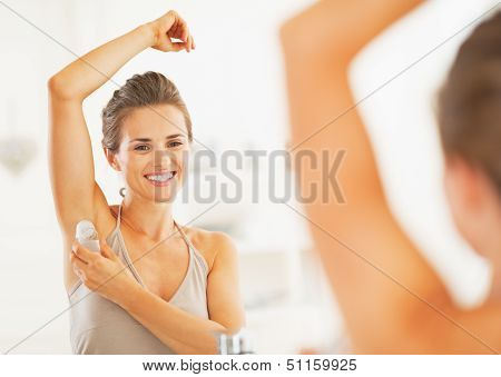 Smiling Young Woman Applying Roller Deodorant On Underarm In Bat