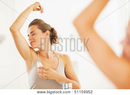 Woman enjoying freshness after applying roller deodorant on underarm poster