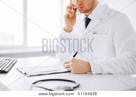 healthcare, hospital and medical concept - male doctor writing prescription paper and capsules poster