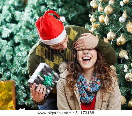 Young man in Santa hat covering woman's eyes while surprising her with gift at Christmas store