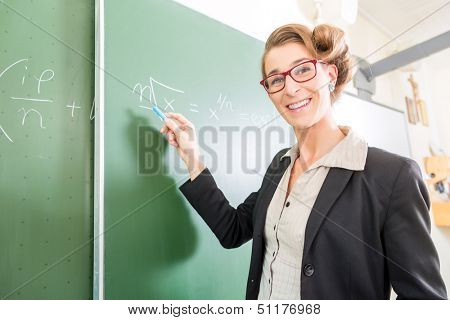 Teacher or docent writing with chalk on the board or  chalkboard or blackboard while math lesson in school class