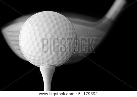 Black and white photo of golf ball on tee with driver in motion - about to make contact. Macro with extremely shallow dof on black background.