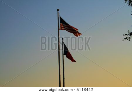 Sunset Over American And Texas Flags
