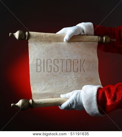 Santa Claus holding his naughty and nice list over a light to dark red background. The list is blank, ready for copy. Only Santa's hands and arms are visible.