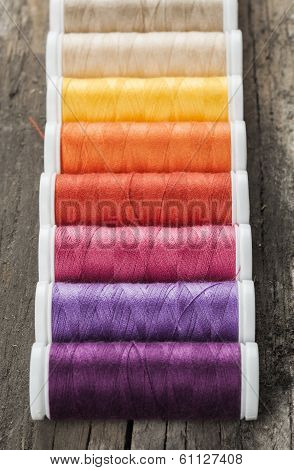 Single row made of color spools of sewing threads, on wooden background
