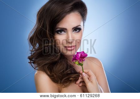 Studio Shot Of A Beautiful Young Woman Holding A Flower