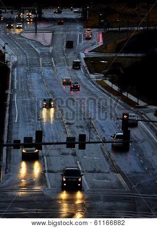 Cars with headlights shinning on stormy wet road driving in rain