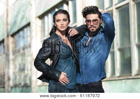 young casual woman posing beside her man and looking away from the camera while holding her hand on his shoulder. he is passing his hand through his hair and looking into the camera