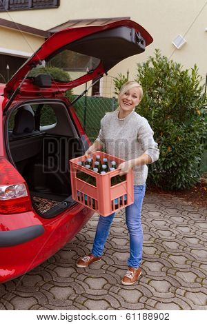 a young woman lifts a crate of bottles from their car. real life prevents back pain and herniated disc