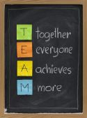 TEAM acronym (together everyone achieves more) teamwork motivation concept color sticky notes white chalk handwriting on blackboard poster