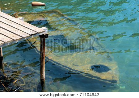Old Rowing Boat Under Water At A Wooden Jetty