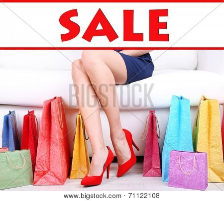 Concept of discount. Woman in red shoes sitting on sofa with shopping bags