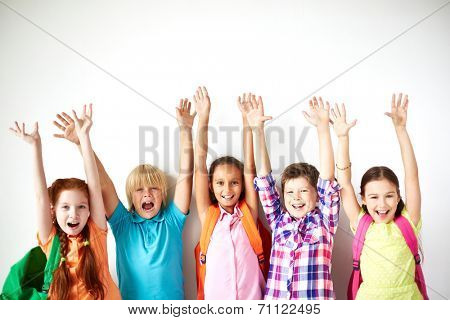 Ecstatic friends with raised arms looking at camera
