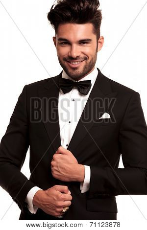 smiling young groom in tuxedo and bowtie holding his suit on white background