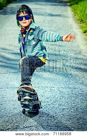 Cool 7 year old boy with his skateboard on the street. Childhood. Summertime.