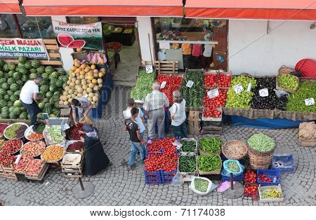 SAFRANBOLU, TURKEY - JUNE 23, 2012: People buy fruits and vegetables on the street market. Locals prefer to buy foods on the market due to cheaper prices and broader assortment