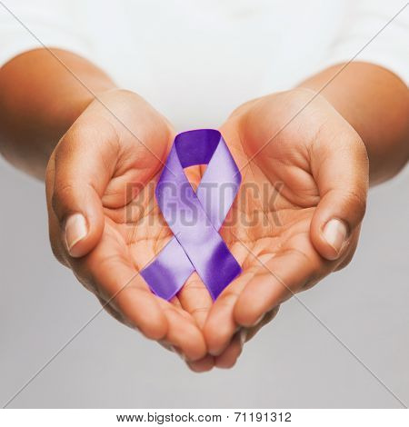 healthcare and social problem concept - womans hands holding purple domestic violence awareness ribbon