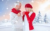 Happy winter couple with mugs against snowy landscape with fir trees poster