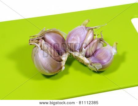 Garlic bulbs on a green cutting board