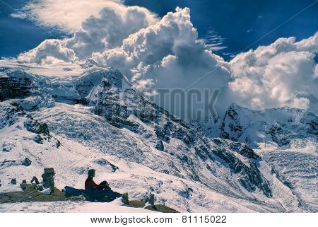 Young hiker sitting in south american Andes in Peru Ausangate with dramatic clouds forming above the mountains poster