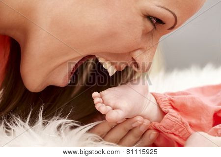 Closeup photo of mother holding and biting tiny bare baby foot. Side view.