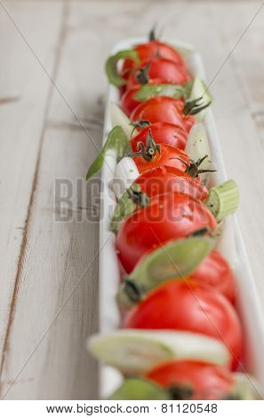 White Elongated Dish Filled With Cherry Tomatoes And Spring Onions