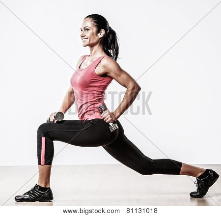 Beautiful woman doing fitness exercise with dumbbellls